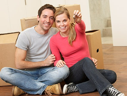 Couple sitting on the floor holding a house key